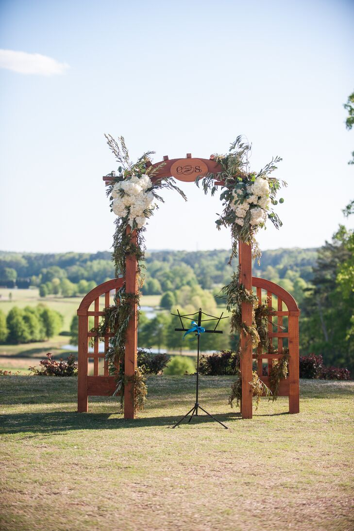 The outdoor ceremony took place under a wooden arbor that was built by Colleen's father and decorated with white hydrangea, berries and greenery.