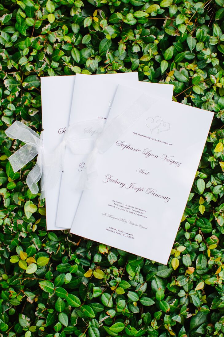 Inspired by Pinterest, the couple had a custom invitation suite designed by 5 Thirteen Designs. Stephanie printed the wedding programs at home and made each table number for the reception, she says.