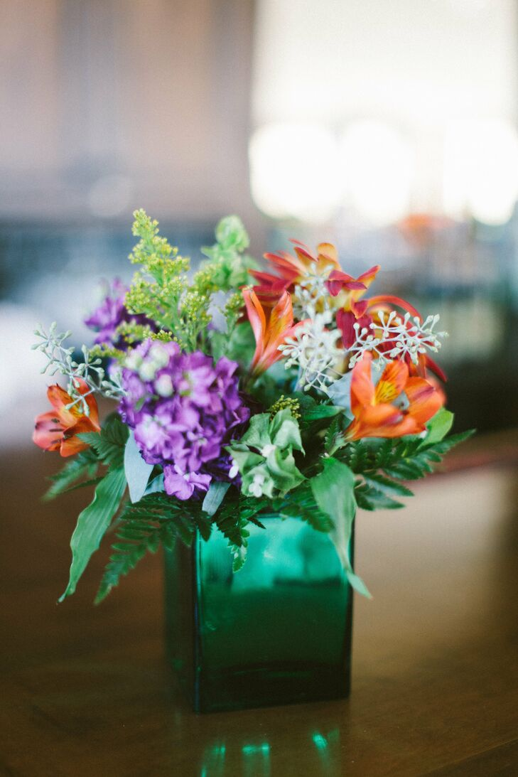 Colorful arrangements of alstroemeria, stock, solidago and seeded eucalyptus were placed in emerald green vases at the reception.