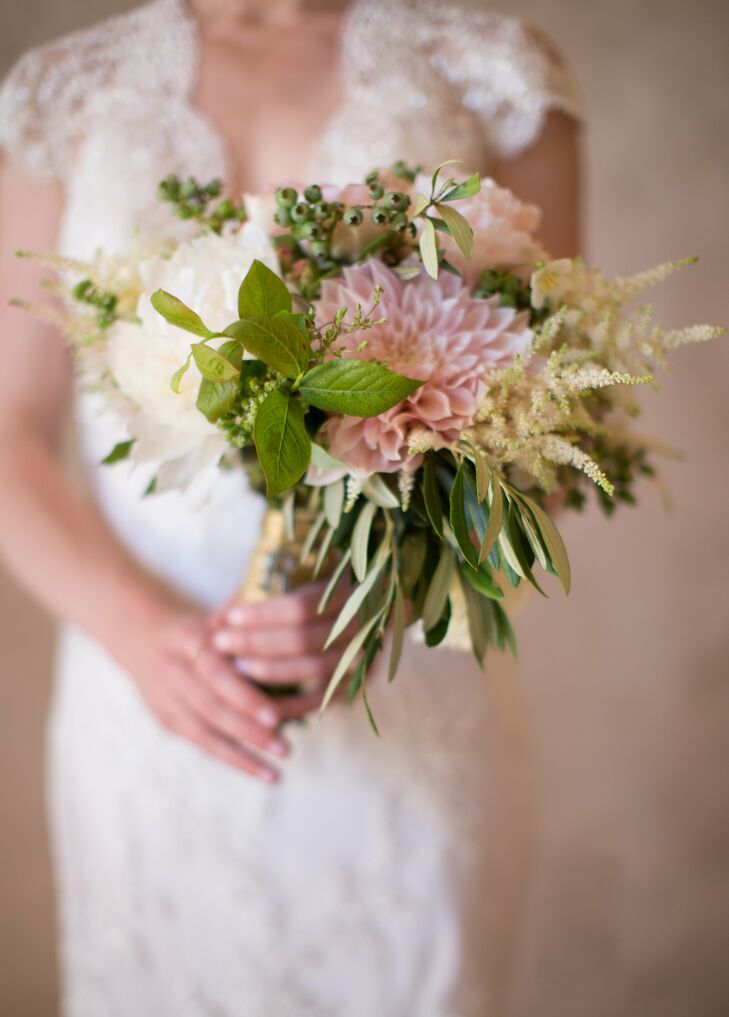 The bride carried a bouquet of textured flowers down the aisle, including blush dahlias, bay leaves and blueberries.