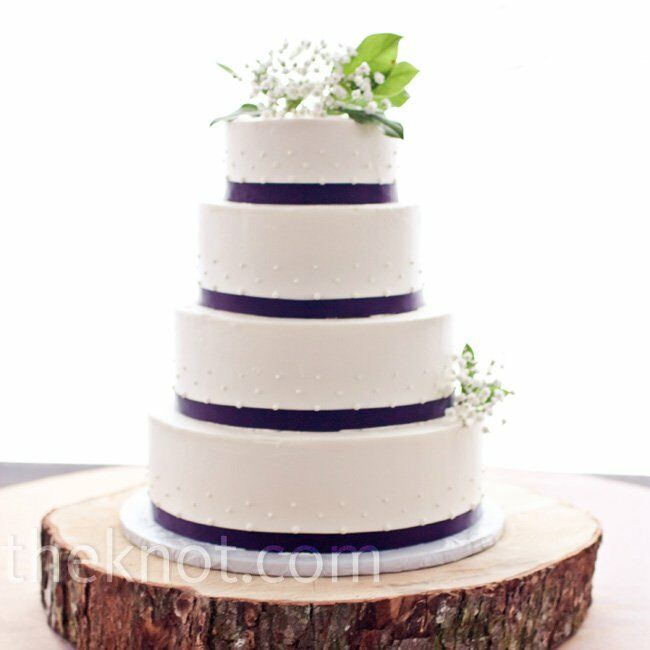 Purple-fondant ribbon wrapped around the polka-dotted confection. A sliver of a tree trunk served as the cake stand.