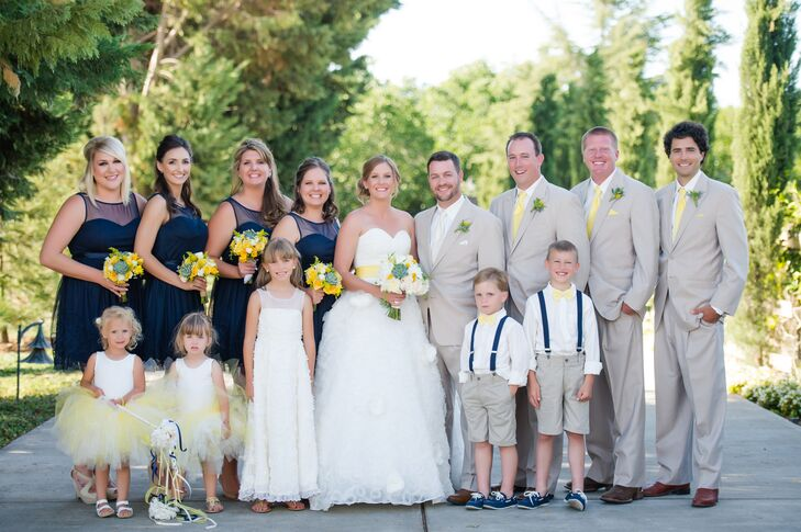 "Claire and Nolan stood with their wedding party, who were dressed in navy blue and tan attire. ""My bridesmaids wore navy blue party dresses from David's Bridal, and they had a little detail on the skirt that matched the swirl pattern on my skirt,"" Claire says. ""The groomsmen wore tan suits with yellow ties, and Nolan wore the same tan suit with an off-white tie."""