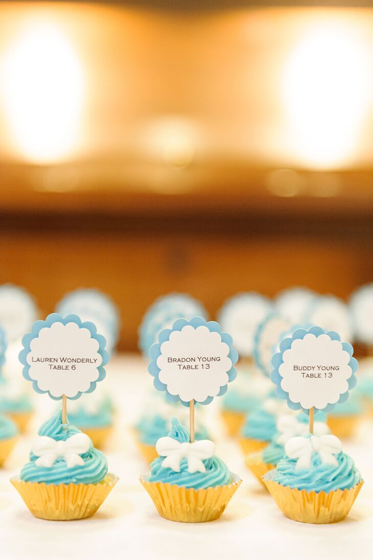 The scalloped escort cards with light blue trim were displayed on min cupcakes baked by Erin. The cupcakes were decorated with light blue frosting and white fondant bows.