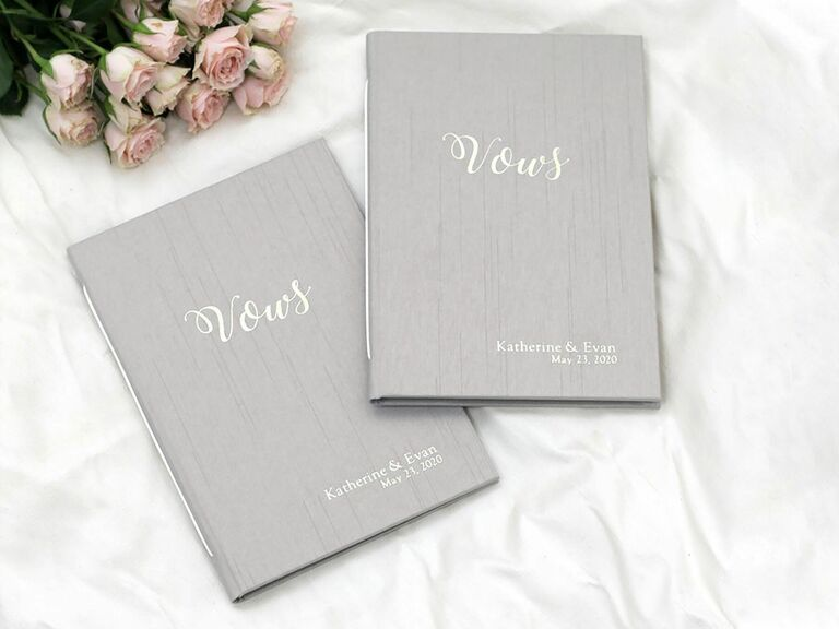 Set of silver silk vow books personalized with couple's names and vow renewal date