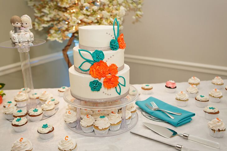The three tier ivory wedding cake was decorated with orange and turquoise fondant flowers and surrounded by cupcakes. The flavor was almond vanilla cake with raspberry preserve filling. The Precious Moments cake topper featured a loving couple in their getaway car.