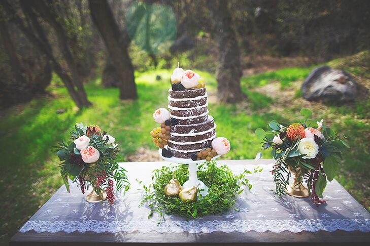 Flanking either side of the delectable naked cake were bunches of cascading vines and full garden roses arranged in elegant brass vases.