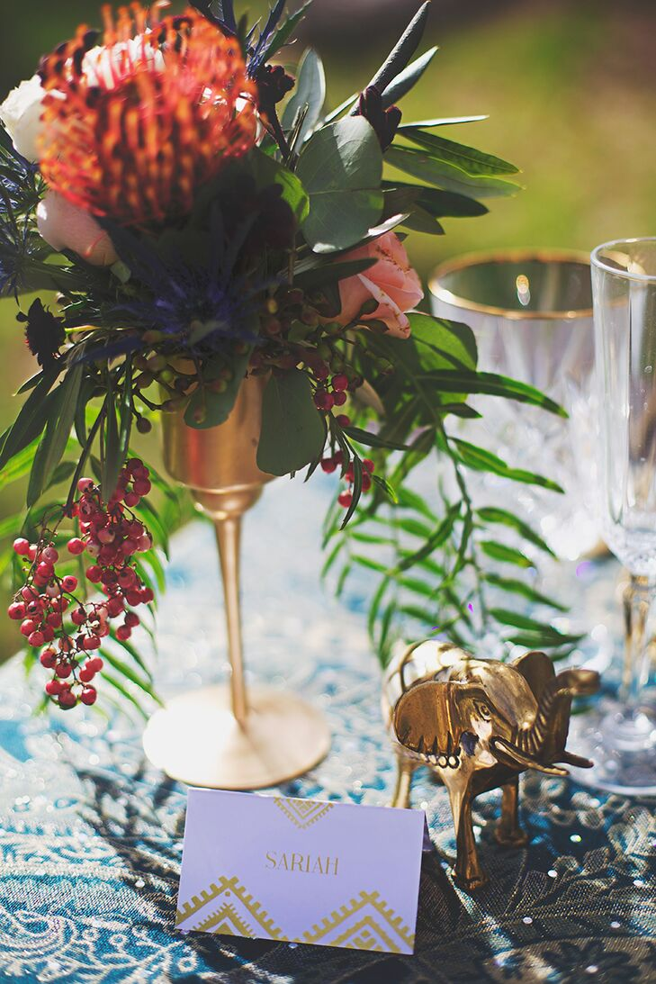 Geometric gold place cards complemented the wedding's invitations and tied in seamlessly with the tabletop's other brass elements.
