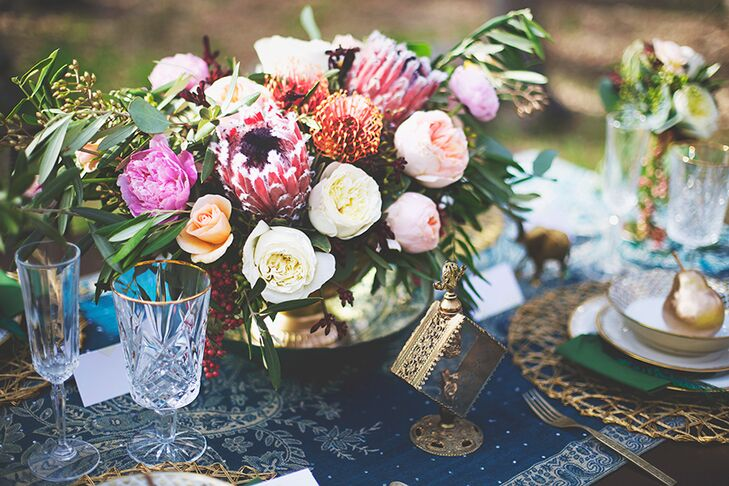 Garden roses, king proteas and pincushion flowers filled refined brass vases for a romantic, bohemian look that anchored the reception decor.