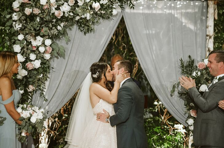 Romantic First Kiss with Greenery, Roses and Draping