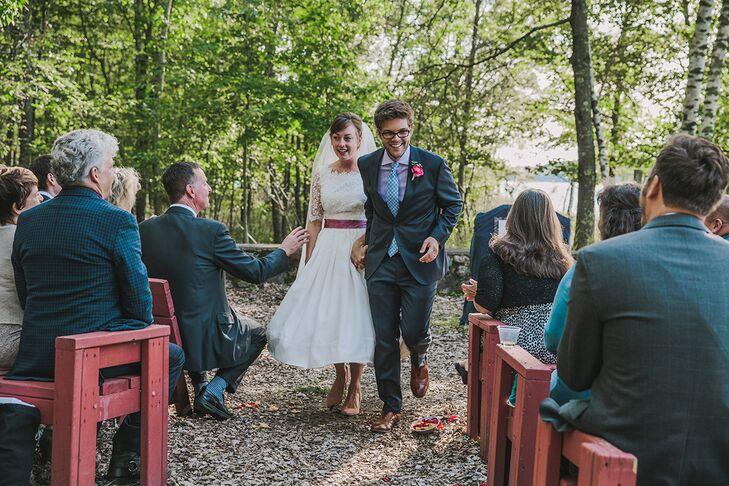 Guests at on camp-style red benches as Sarah and Finn exchanged vows under thick foliage.