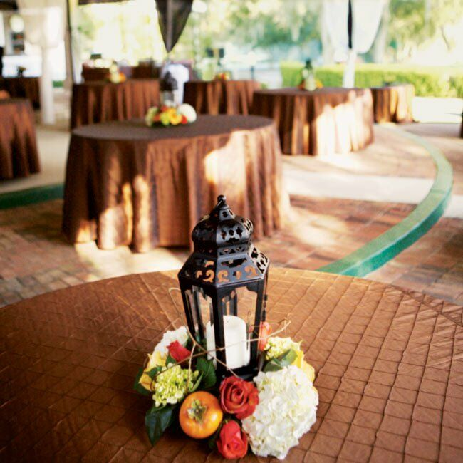 Amber and Chad's dinner tables were set with quilted, burnt copper–colored linens and centerpieces of lanterns surrounded by moss, flowers, and persimmons sat atop the tables.
