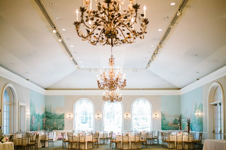 The reception was held in the Garden Terrace Room at the botanical garden. The room features vaulted ceilings, ornate gold chandeliers and beautiful landscape paintings on the walls. For the reception, Allison and Alistair arranged the room with round dining tables and gold chiavari chairs surrounding the dance floor.