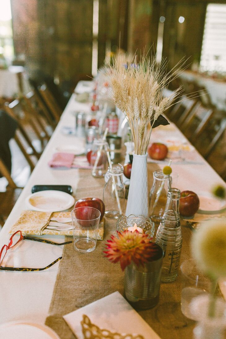 Lined with ivory linens and burlap runners, the tables were set with handmade vintage-inspired napkins, milk bottles and apples. Various vases, bottles and tin cans were used as centerpieces. Small votive candles filled with corn kernels and more apples also accented the settings.
