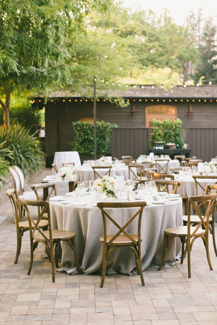 Taking advantage of the breathtaking setting, Jessica and Brent treated their family and friends to an al fresco soiree, starting with a cocktail hour on the terrace, followed by dinner under the stars. Round tables draped in neutral linens were styled alongside French country chairs and topped with fresh bunches of textured ivory, blush and peach blooms. Bistro lights hung overhead, casting warm light over the outdoor scene, and providing the decor with a charming Mediterranean flair.