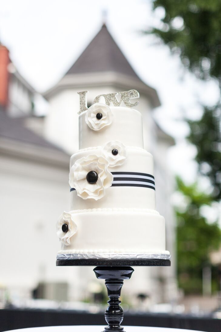 "The main ivory wedding cake stood three tiers tall and had black-and-white sugar flowers decorating the surface. The middle layer of the cake had a black-and-white-striped ribbon wrapped around the middle. The cake was topped with a silver sparkly  ""Love"" sign, and the entire dessert was positioned on a simple black cake stand."