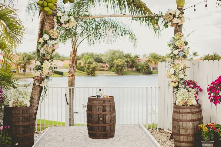 The wedding arch brought Florida's palm trees into their ceremony! Each tree was connected by one strand of birch wood and covered with tons of flowers. White, green and pink hydrangeas, white roses, greenery and baby's breath accented each one. Wooden barrels on both sides were also topped with similar arrangements.