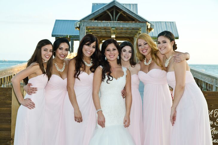 The bridesmaids wore WToo strapless light pink floor-length dresses with a sweetheart neckline. Each paired the dress with a pearl necklace.