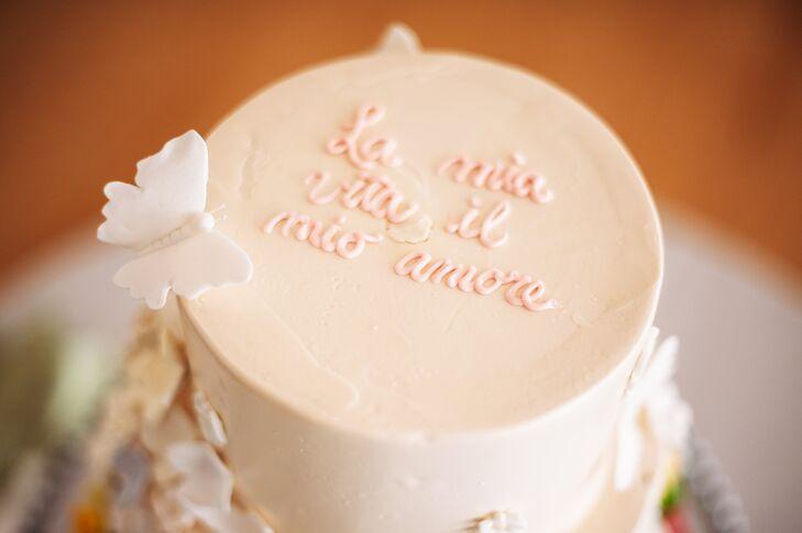 "On the top of the ivory wedding cake by Bella Christies read ""La Mia Vita il Mio Amore"", which translates from italian to English to ""My Life, My Love."""