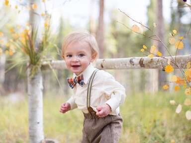 Toddler in nature wearing brown pants, a white shirt, striped suspenders and a plaid bow tie