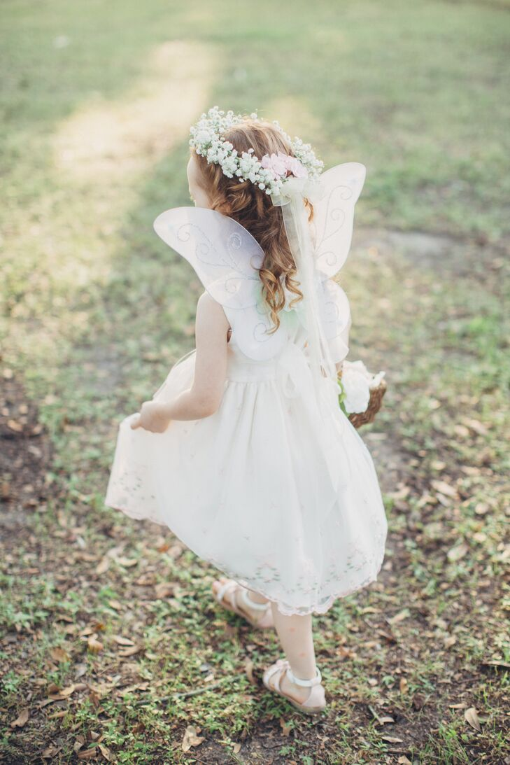 The flower girl dressed like a fairy, complete with a baby's breath flower crown and butterfly wings with her white sundress.