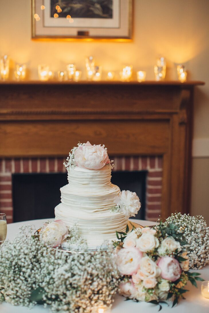 Blush peonies and baby's breath added soft, romantic accents to the three-tier white ruffled wedding cake.