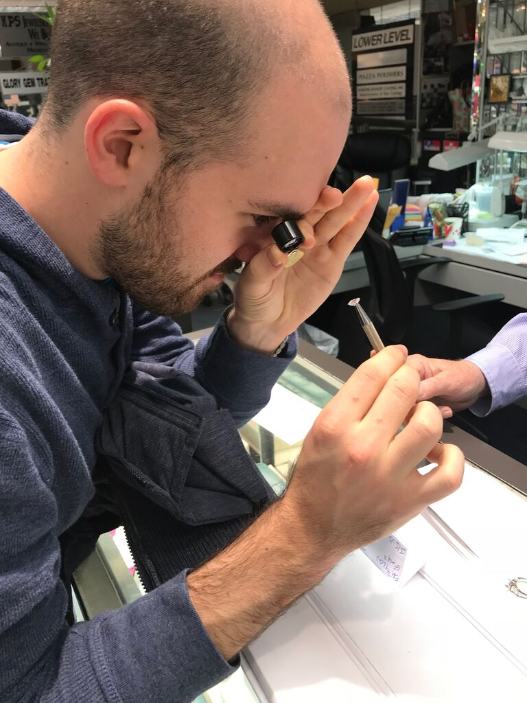 man looking at diamond with magnifying glass