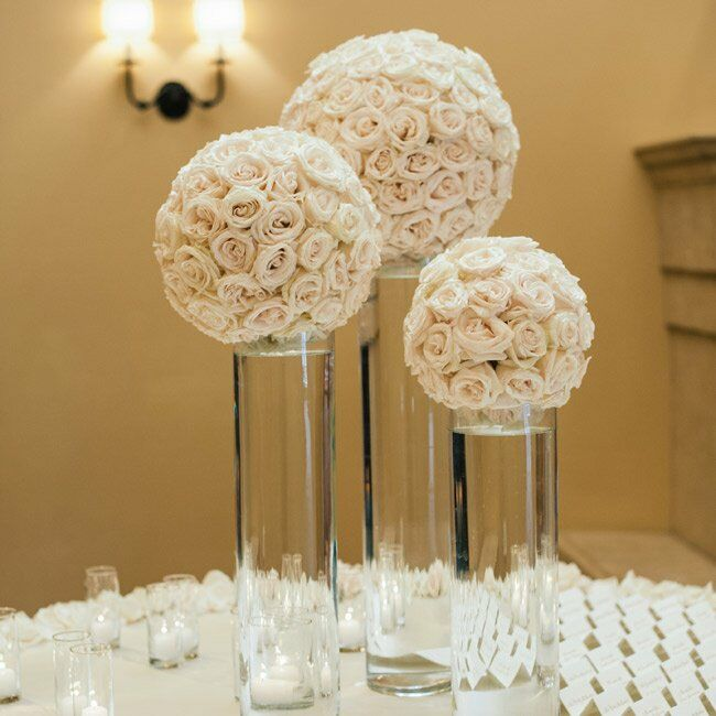 Set at the center of the escort card table were three ivory rose pomanders arranged on top of tall hurricane vases that added a romantic, yet modern touch to the display.