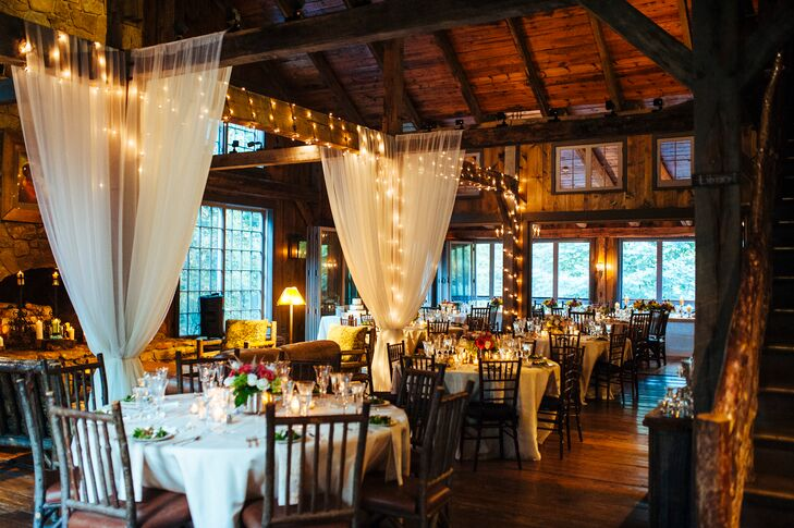 White drapes and fairy lights gave the rustic reception room at Thorpewood in Thurmont, Maryland, a soft, romantic look.