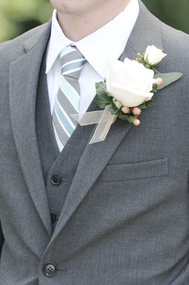 Frankenmuth Florist created simple white rose boutonnieres adorned with pink berries to go with the gray suits and the mint green from the striped ties worn by the groom and his groomsmen. They added a lighter accessory in contrast to the pastel pink and white bridal bouquets.