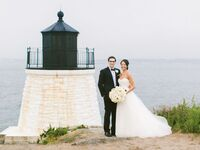 wedding couple standing with lighthouse