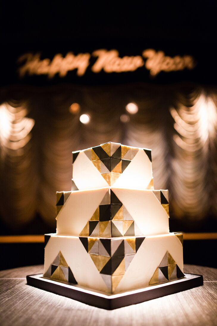 The three-tiered ivory wedding cake was designed by Pretty Please bakery, and was decorated with gold and black geometric shapes.