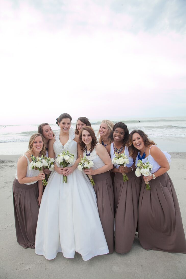 Alissa wanted to choose an outfit for her bridesmaids that would keep them cool and comfortable during the beachfront ceremony, while working with the wedding's neutral color palette. She opted for brown maxi skirts and white tank tops, which the girls dressed up with their own navy necklaces.