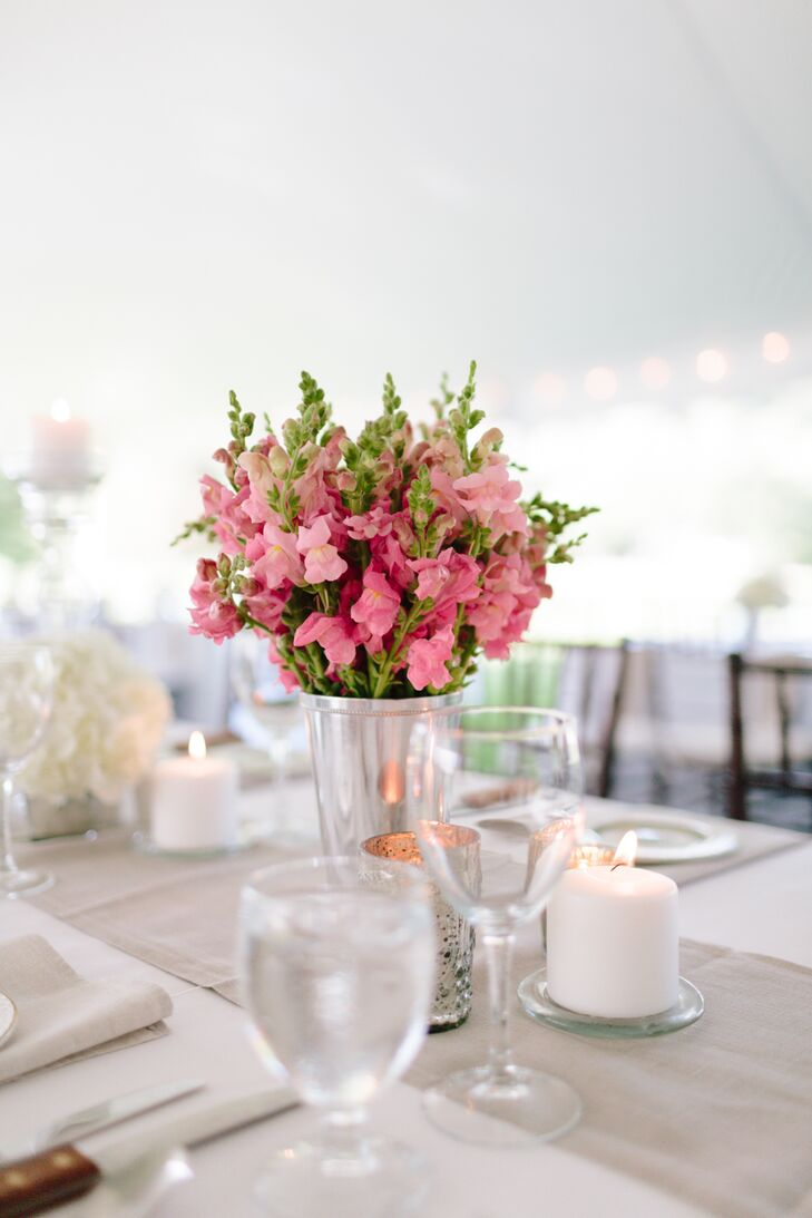 A lush arrangement of pink sweet peas were displayed in silver vases for the centerpieces, adding a soft, romantic touch to the table decor.
