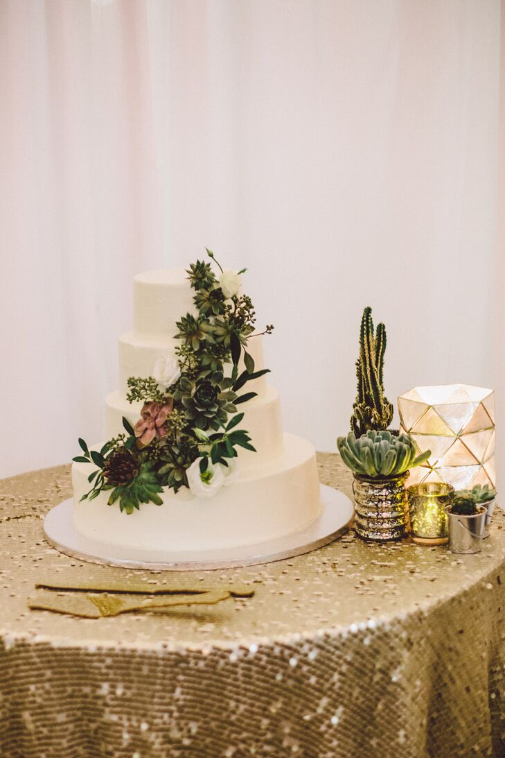 The couple chose a white wedding cake with buttercream frosting and decorated with a cascade of succulents.