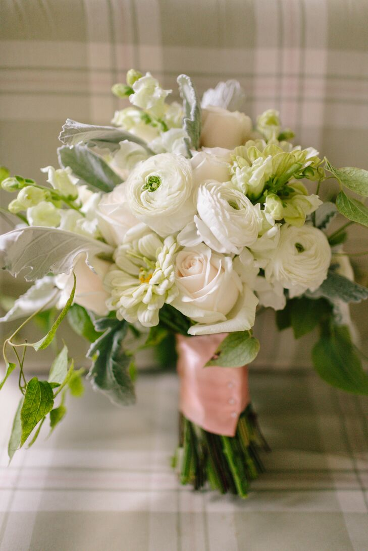 The lush white bridal bouquet was an elegant mix of zinnias, roses and ranunculuses. The bouquet was wrapped with a light pink satin ribbon.