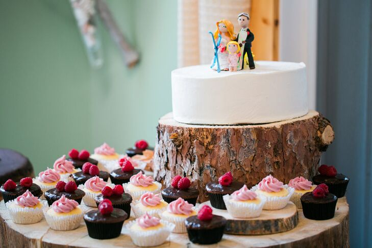 Dessert was displayed on tree stumps at the reception. The lemon-raspberry wedding cake was topped with figurines of Christine, Mitch and their daughter in ski gear. Surrounding it were cupcakes created by Christine's sister.