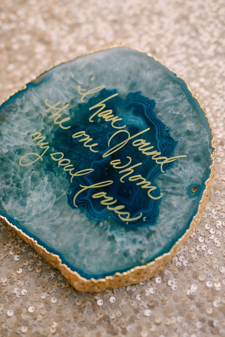 """Agate decor took the natural theme one step further with gold borders and gold calligraphed quotes on the rich blue surface. This agate, beside Madelyn and Joseph's cake, read """"I have found the one whom my soul loves."""""""