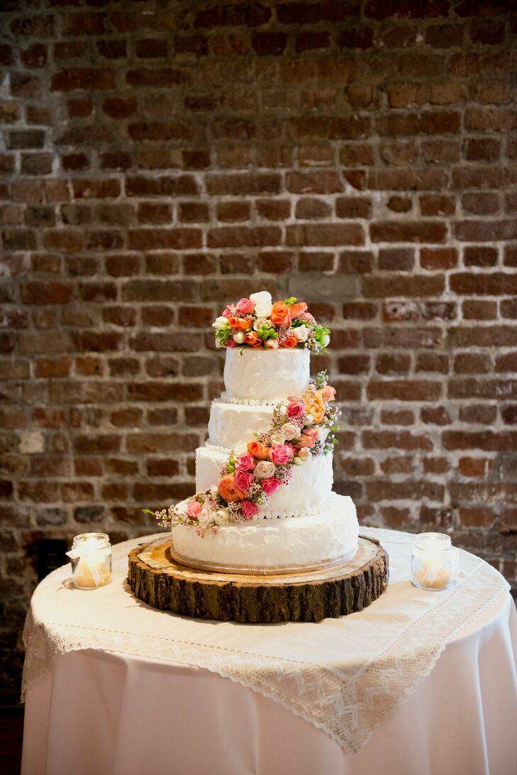 Wedding Cake On Wooden Slab With Bright Flowers