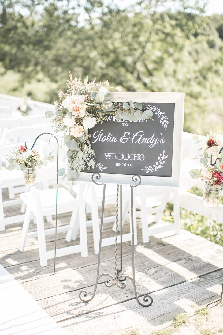 A chalkboard sign decorated in flowers and greenery announced Italia and Andy's wedding at Winterset Cidery in Winterset, Iowa.