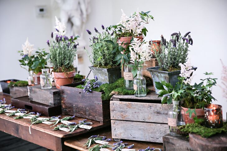 Escort cards made by The Papery were assembled on a wooden farmhouse table, surrounded by wood boxes with astilbe and lavender in pots and glass vases, created by TableArt.