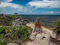 woman sitting on cliff in tulum mexico