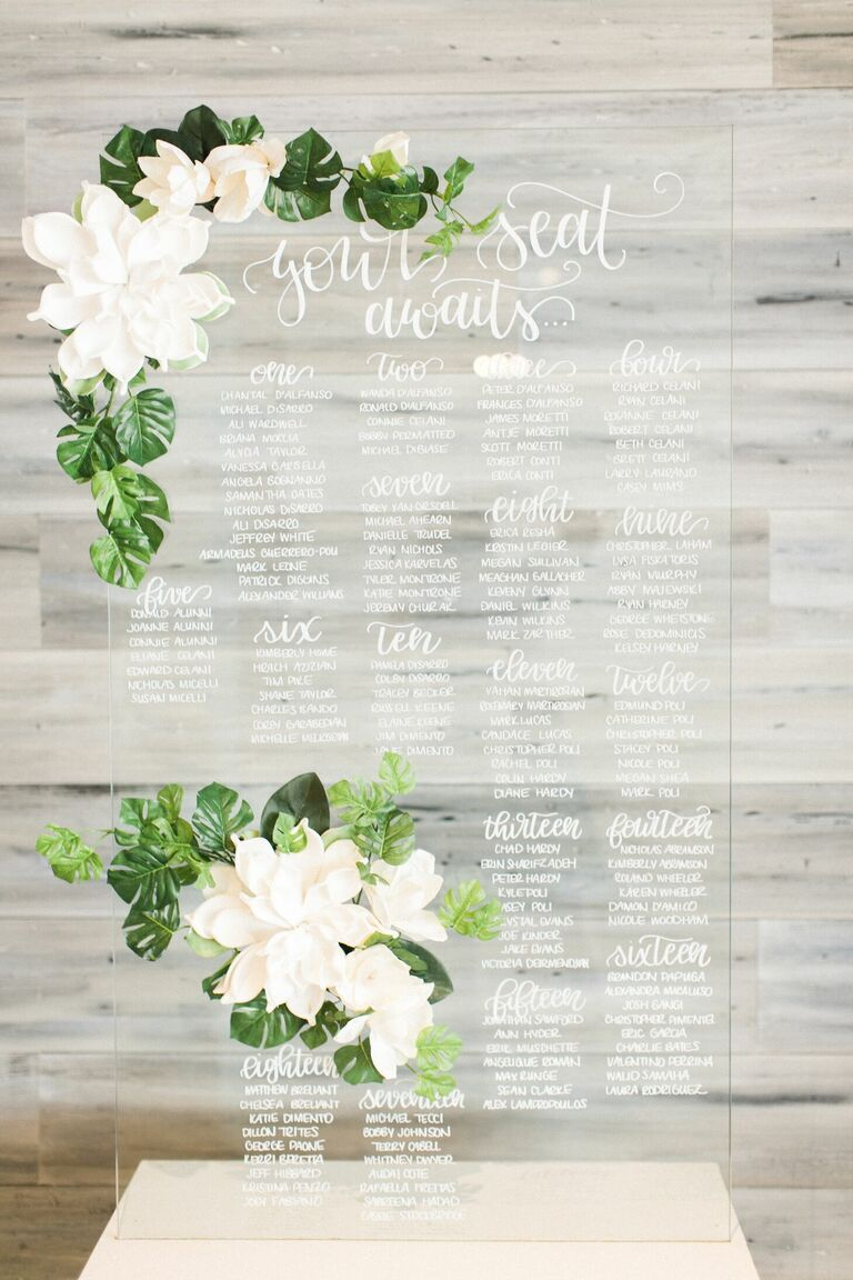 Calligraphed acrylic seating chart with fresh flowers