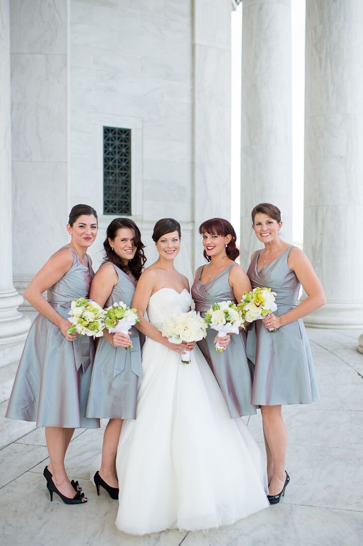 For the winter wedding, Joan's bridesmaids wore knee-length silver dresses by Alfred Sung from Nordstrom Bridal Shop. White and green bouquets with cymbidium orchids completed the look. At the reception, all of the bridesmaids ditched their matching black heels and changed into sparkly Toms for dancing.