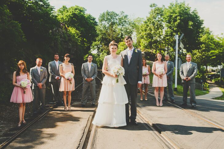 Katie and Justin stood on the tracks with their wedding party, with bridesmaids dressed in knee-length pink dresses while the groomsmen wore gray suits with ivory ties. The groomsmen matched the groom's apparel, and the ties matched the bride's layered wedding dress.