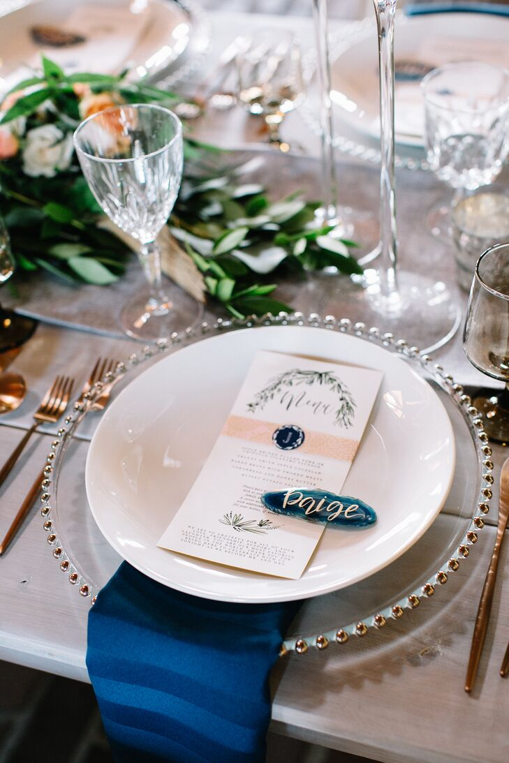 With a large head table filled with their closest family members and friends, Hope and Nick incorporated name cards into each place setting. Fox and Sparrow hand-lettered the names of each guest in gold ink onto blue agate stones, which were then placed atop each custom-designed menu for an elegant, organic look.