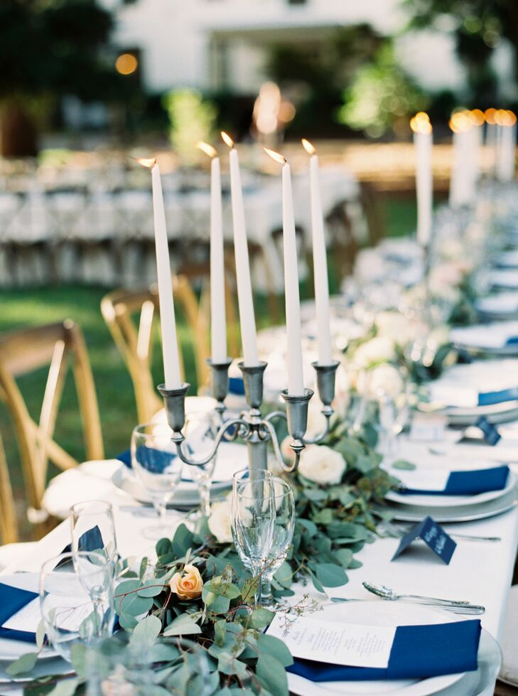 To make the decor even more romantic, Laurie and Brian worked with Missy Gunnels Flowers to line their tablescape with candlelight. Tall silver and white candelabras were set alongside a garland of eucalyptus and separated by orange, pink and white roses.