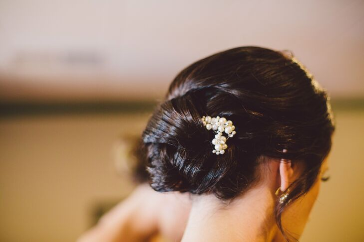 The bride wore her hair in an elegant low chignon, which she accented with a pearl and crystal hair pin.