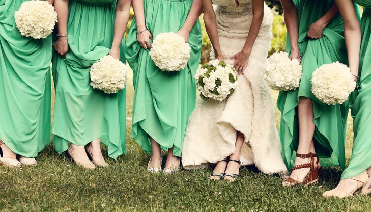 The bridesmaids wore floor length emerald green gowns with sweetheart tops and their own choice of shoes. Their footwear ranged from wedges to heels. rn