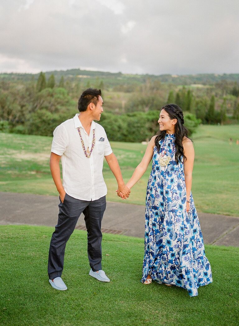 Couple holding hands on hill in Hawaii