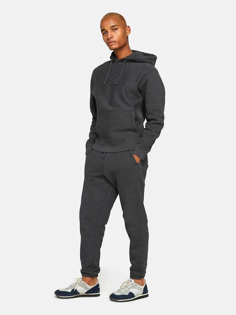 Man wearing snug cotton sweatpants and matching hoodie in black